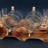 Pálinkás készlet két hordóval, 6 pohárral natúr színű égetett mintájú fa állványon.